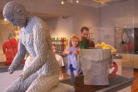 LEGO ART: Casey Wolfe, a producer, holds his daughter, Emma Wolfe up to view the sculpture made entirely out of Lego blocks by Nathan Sawaya on exhibit at the Forest Lawn Museum Friday.