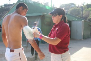 ICING IT UP: Athletic trainer Claudia Alvarez wraps the arm of Vaquero's star pitcher Angel Rodriguez after Rodriguez pitched all nine innings against L.A. Mission College.